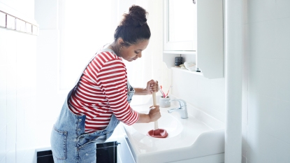 Woman using a plunger for her sink
