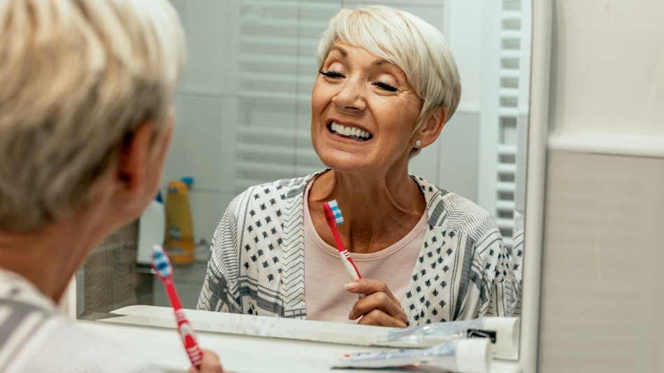 Woman looking in the mirror after brushing teeth