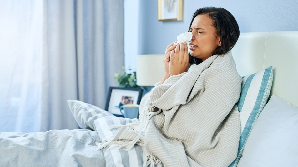 woman in bed sneezing