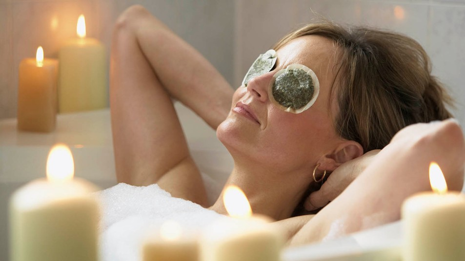 woman relaxing in bubble bath with candles