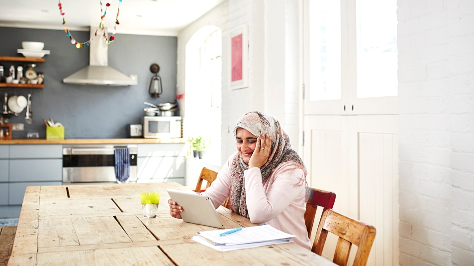 woman using ipad at kitchen table and smiling