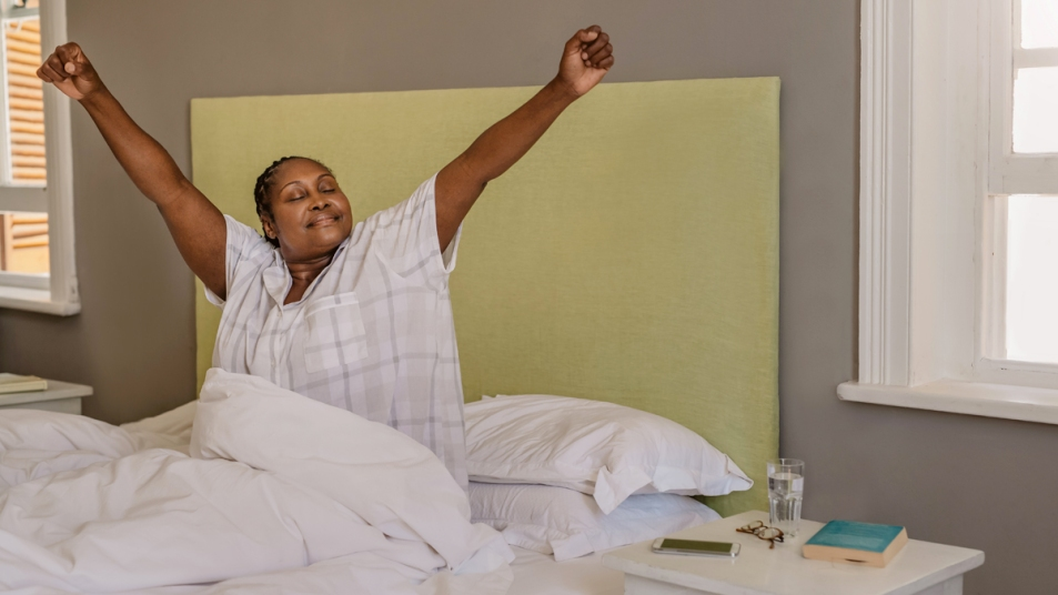 Woman sitting up and stretching arms out in bed