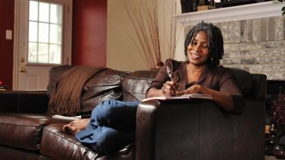 woman sitting on sofa journaling