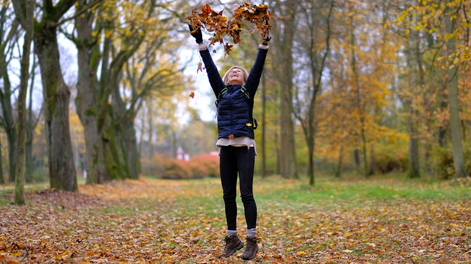 woman jumping in fall leaves