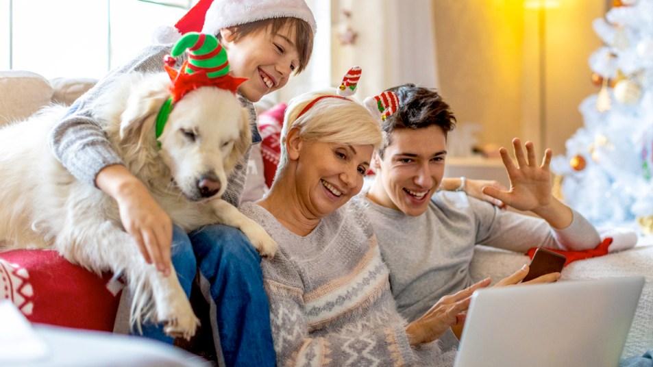Mom and sons waving to video call on Christmas