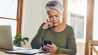 Woman looking at bills and calculating costs