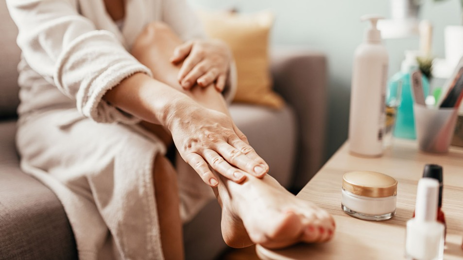 woman rubbing her feet with lotion