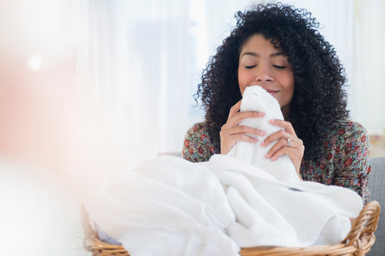 Young woman smelling her freshly cleaned white towels.