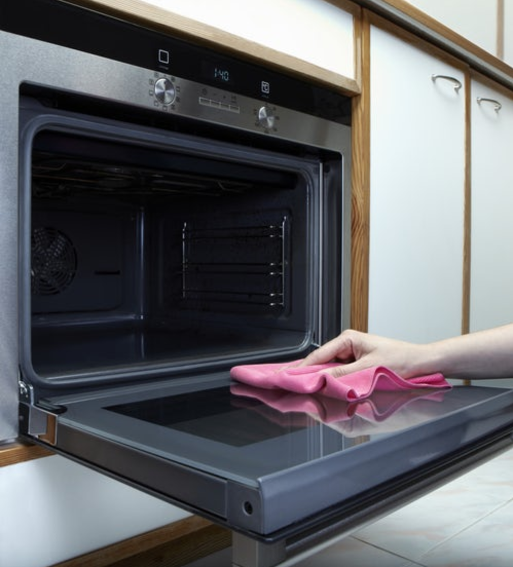 hand cleaning oven with pink washcloth